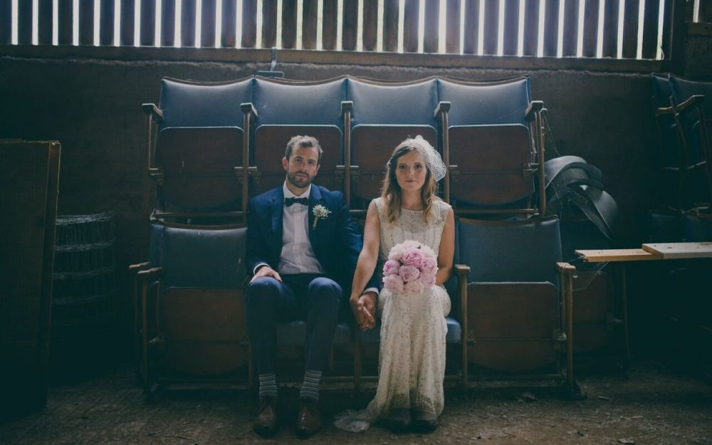 Newly-wed couple sit on vintage theatre chairs at Lyde Court Wedding venue in Hereforshire